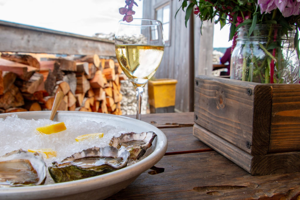A plate of oysters on ice and a glass of wine